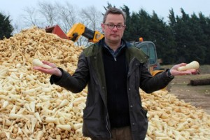 Hugh Fearnley-Whittingstall yn sefyll o flaen tomen o bananas annerbyniol (as you do..)